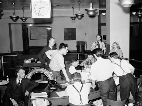 Reporters stand aroud a semicircular desk littered with papers. Threre are also two phones on the desk. The clock hanging from the ceiling reads 2:34.