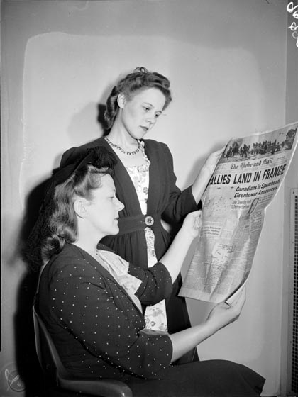 Two women look at an edition of the Globe and Mail. The headline reads, ''Alllies land in France: Canadians in spearhead, Eisenhower announces.'