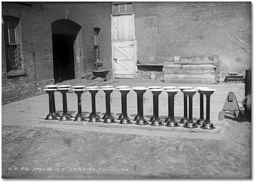 A row of freestanding cast-iron fountains, about three feet high, with white basins at the top.