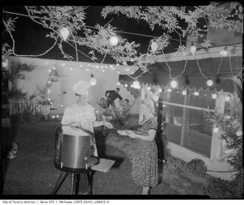 In a backyard illuminated with strings of lights, a man at a barbeque puts food on a plate held by a woman.