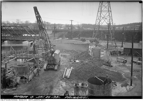 Construction on a pier in a river, with a steel bridge in the background.