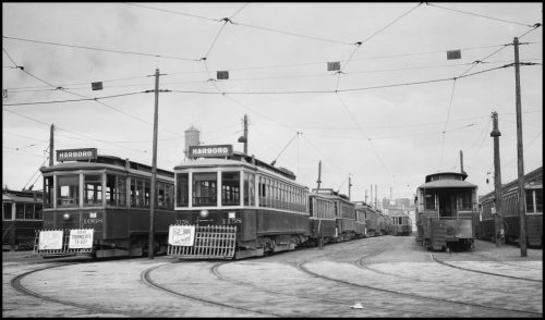 Rectangular streetcars with the word Harbord on the front lined up.