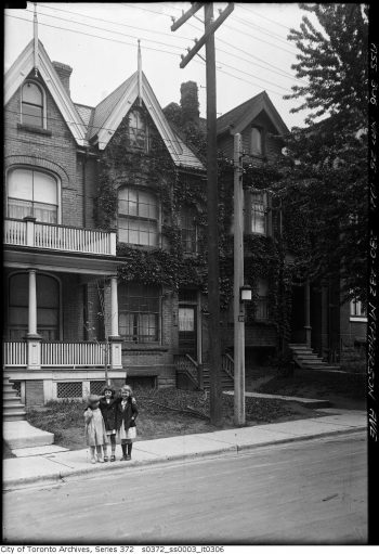 Three small girls stand on the sidewalk in front of a house. A streetlight is attached to the concrete pole beside them.