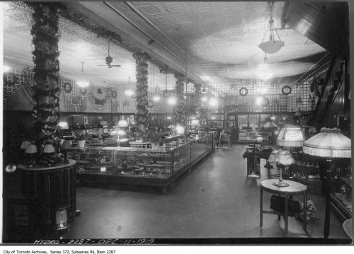 Store interior with wooden and glass cases, and many ceiling and floor lamps.