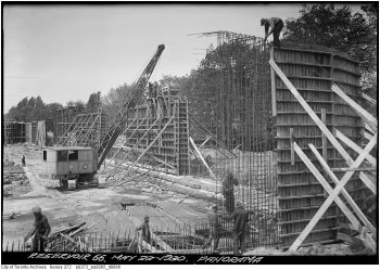Workers and a crane erect a two-storey-high rebar form for concrete.