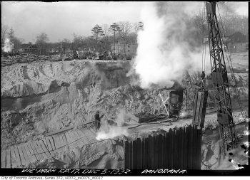 Steam-powered construction equipment on cleared bare ground.