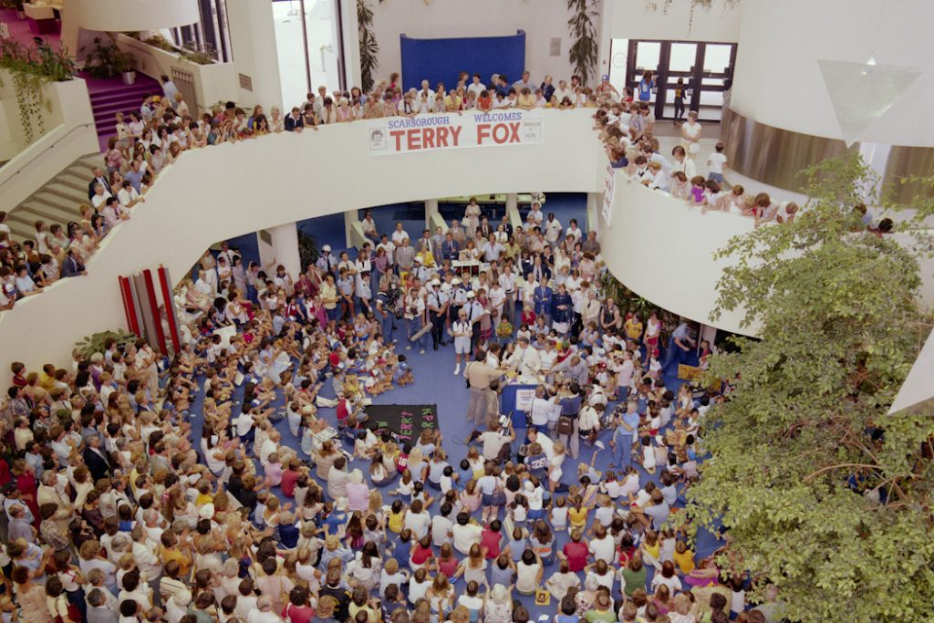 A picture of inside Scarborough Civic Centre of Terry Fox and hundreds of people gathered around