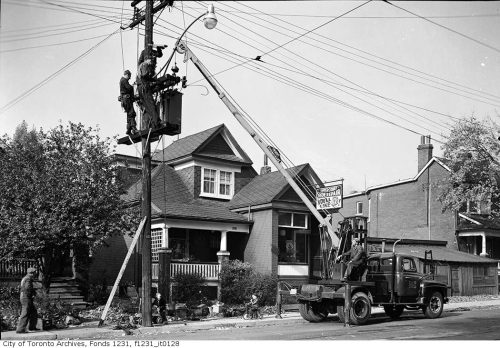 Workers use a crane truck to reach a streetlight in a residential area.