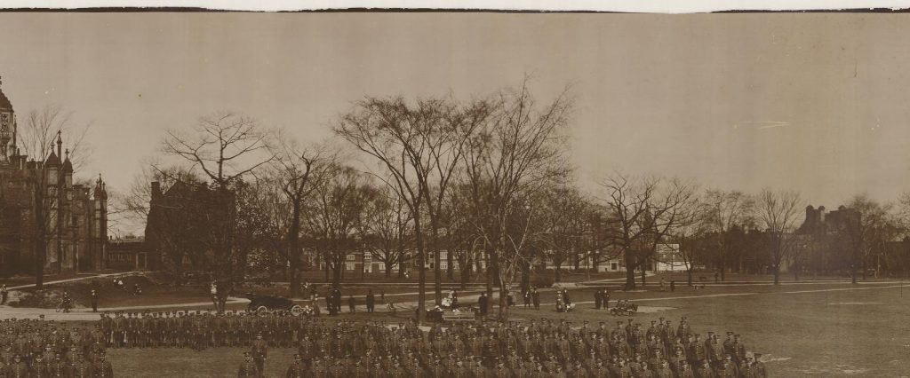 Men in armed forces uniforms lined up in the grounds of a large school.
