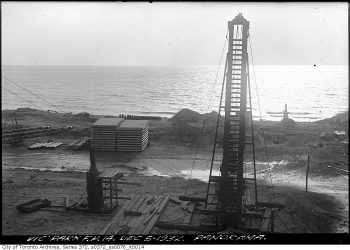 Construction materials stacked on a bare area near the lake beside a vertical conveyor belt.