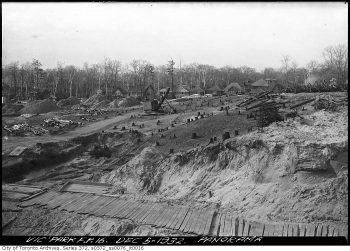 Machines clearing trees from section of land, with houses in the background.