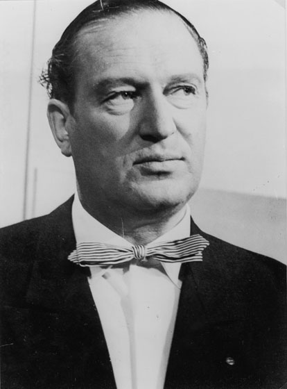 A middle-aged white man wearing a dark suit and bow tie