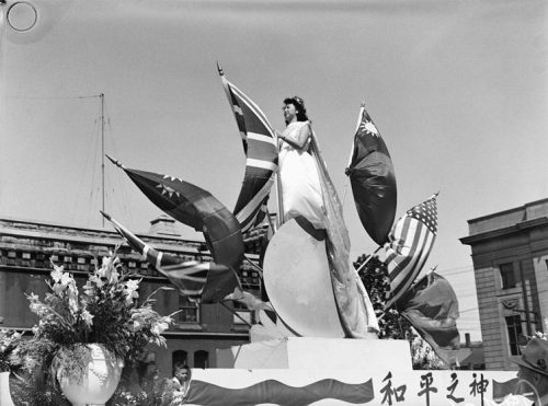 A Chinese woman stands on a parade float surrounded by flags.