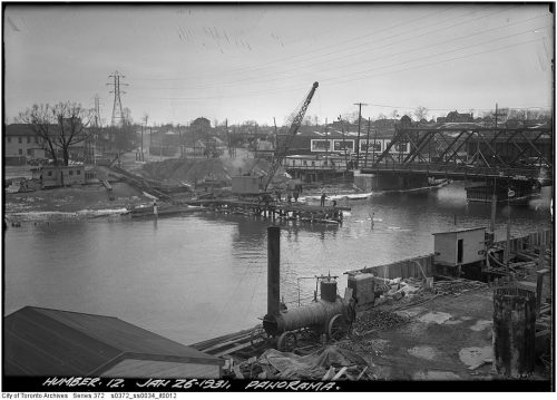 Construction equipment and concrete forms with a steel bridge over a river in the background.