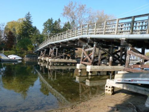 Modern photograph of the Algonquin Island Bridge showing it sitting on top of concrete and wooden stilts.