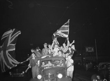 People crowded into the back of a pickup truck cheer and wave large Union Jacks.