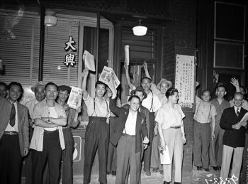 Chinese men in front of a storefront hold up newspapers.