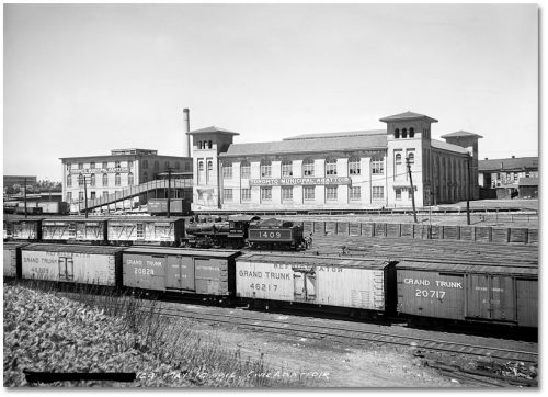 Two two-storey white brick buildings with large windows, and trains on railway tracks in front of them.