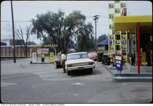 Man getting out of a car in front of a bright yellow gas station building.