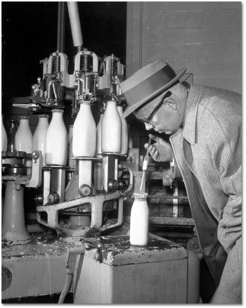 A man uses a syringe to pull a sample of milk out of a bottle, with an assembly line of bottles in the background.