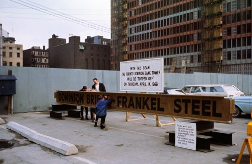People sign a large steel girder propped up on blocks.