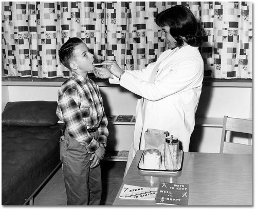 In a medical office, a woman in a lab coat opens a boy's mouth with a tongue depressor.