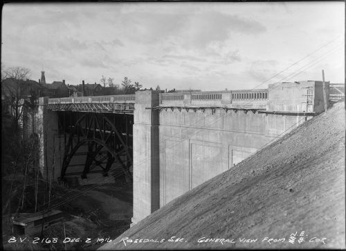 Concrete bridge with arched metal supports.