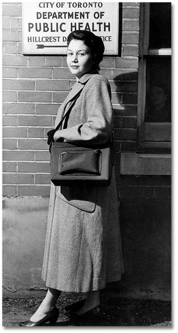 Woman in long coat, carrying large bag.