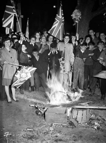 Adults and children wave flags and watch a small bonfire.