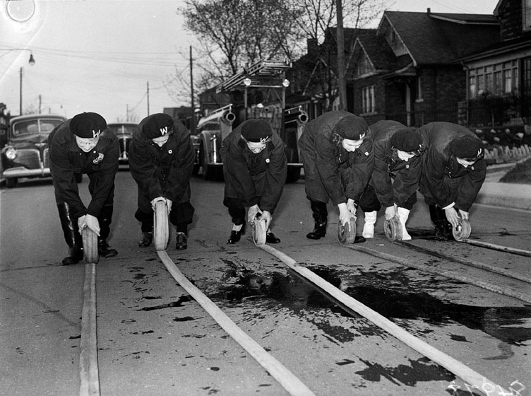 Women roll up long hoses on the ground.