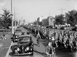 Men in army uniforms march along a road. Children on bicycles ride beside them.
