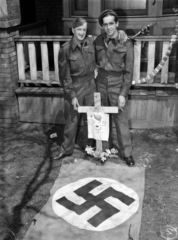 On a lawn, two men in army uniforms display a mock grave with a Nazi flag and a cross gravemarker that reads To Hell With Hitler.