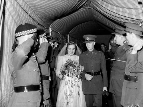 A bride and a soldier walk between two rows of people under a tent.