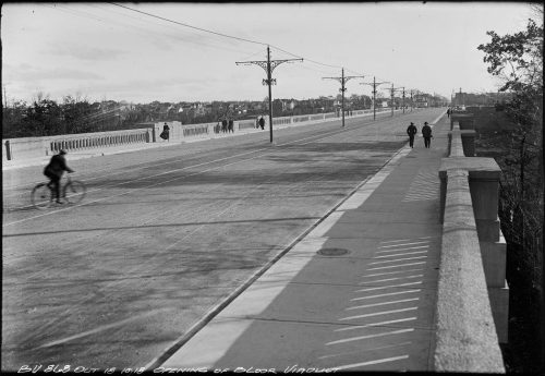 Roadbed of viaduct with pedestrians and a cyclist.
