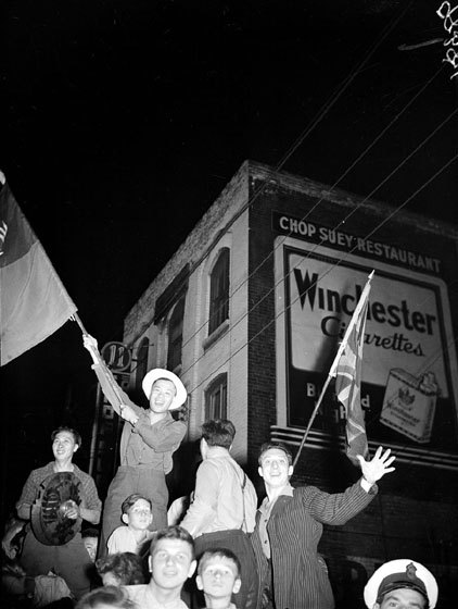 On the street at night, a smiling Chinese man waves a Chinese flag, and a Caucasian man waves a Union Jack.