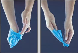 hands removing a latex glove. Reach under the second glove and peel away.