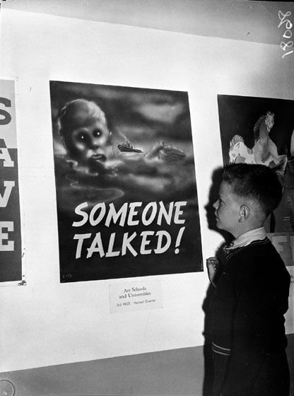 "Boy standing in front of a poster showing a sinking ship and the words ""someone talked""."