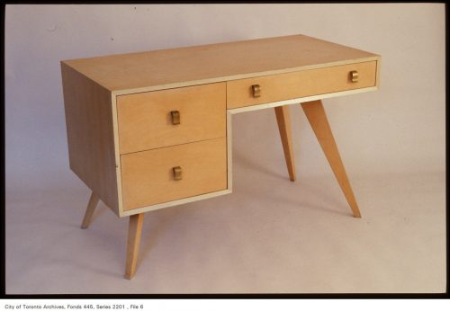 Blonde wood desk with angled legs and three drawers.