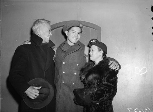 A Chinese Canadian man in military uniform has his arms around an older man and woman.