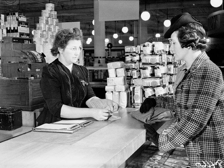 A customer purchases something at a counter stacked with bags of coffee. The cashier is tearing a ticket out of a book of ration stamps.