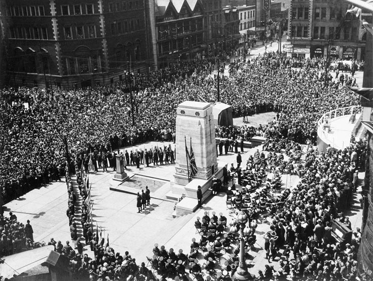 Crowd at Old City Hall stone cenotaph seen from above.