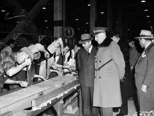 Workers work at a long bench while men in suits look on.