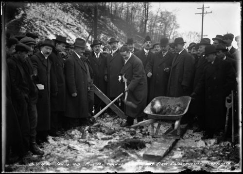 Men in suits and coats surrounding a man shovelling earth into a wheelbarrow.