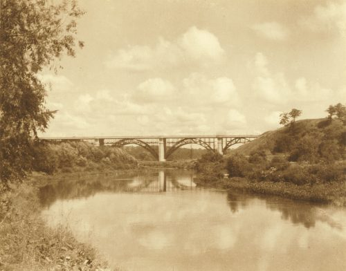Viaduct with arched metal supports seen with river and trees in the foreground.