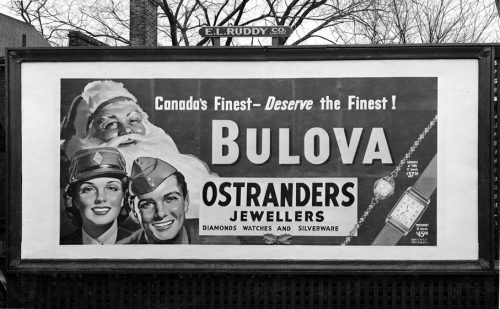 Billboard showing man and woman in armed forces uniforms with Santa Claus.