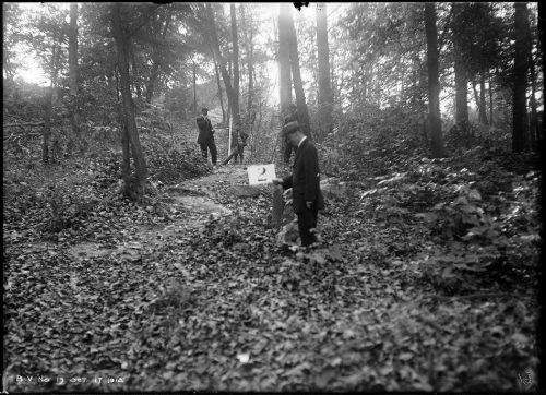 Men in forest, one holding sign.