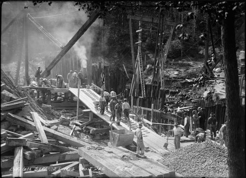 Busy construction site with men transporting supplies up a wooden ramp in wheelbarrows.