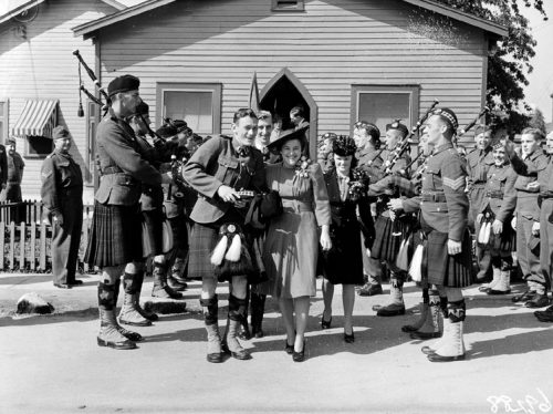 A woman in a dress and a man in a kilt walk between two rows of soldiers with bagpipes.
