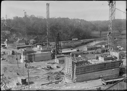 View over valley showing large oval concrete piers being built.