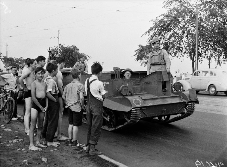 Boys in casual clothes and bathing suits watch as soldiers drive along the road in a tank-like gun carrier.